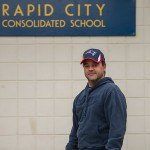 2013 winner Ryan Nevin from Rapid City Manitoba standing next to the Rapid City Elementary School.
